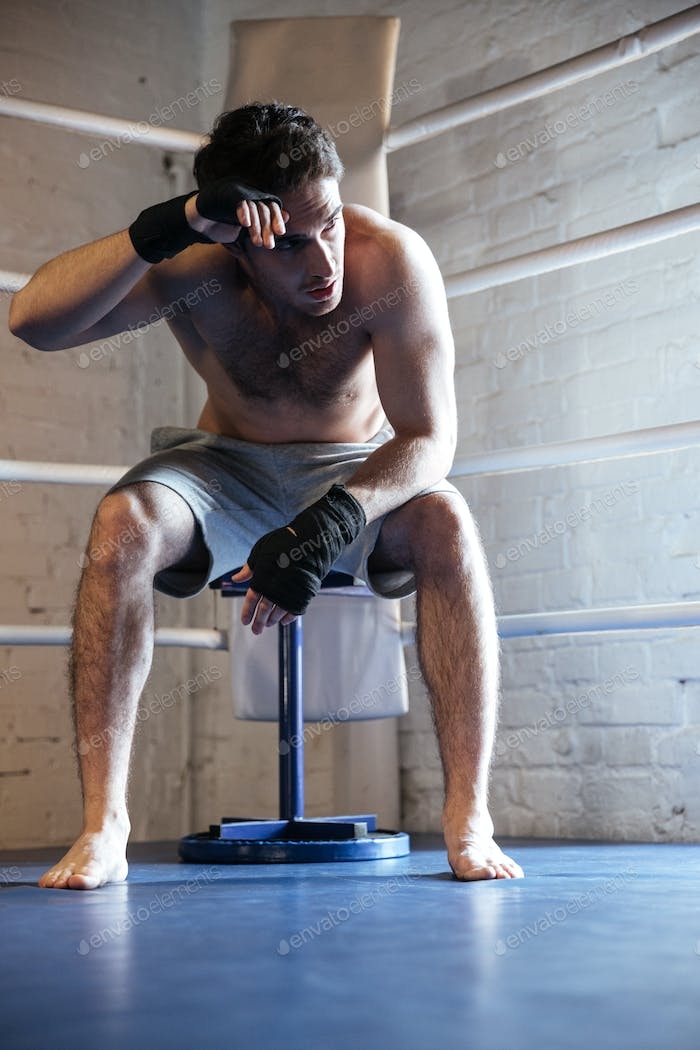 Tired boxer wiping the sweat while sitting on ring
