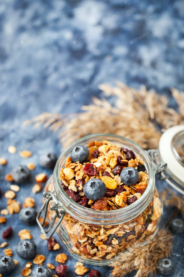 Homemade granola in jar and fresh blueberry