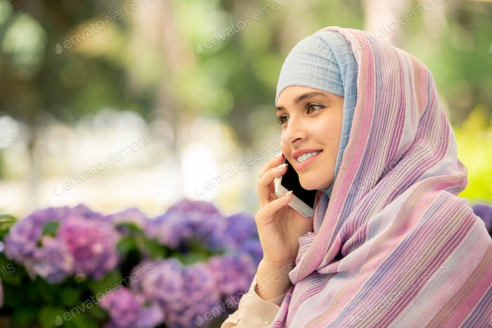 Happy young muslim female with smartphone phoning someone