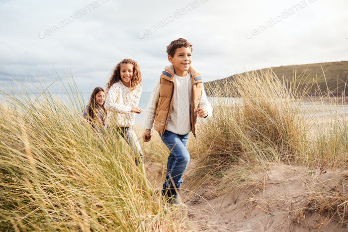 Three Children Having Fun Exploring In Sand Dunes On Winter Beach Vacation