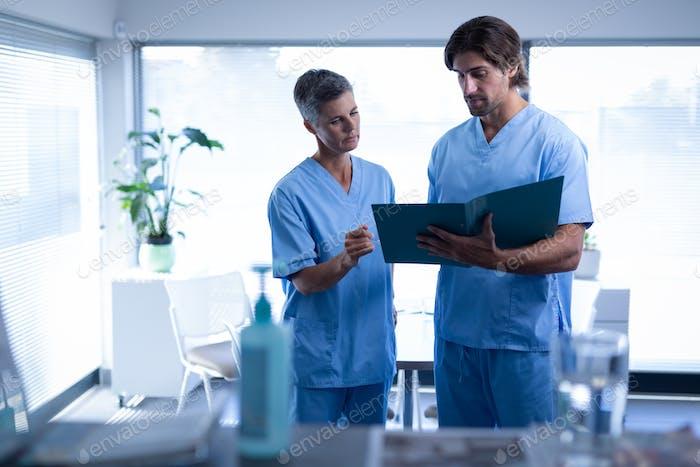 Vorderansicht der kaukasischen Chirurgen diskutieren über medizinische Akte in Klinik im Krankenhaus