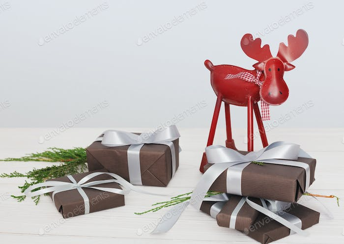 Christmas present boxes and deer on white wood background