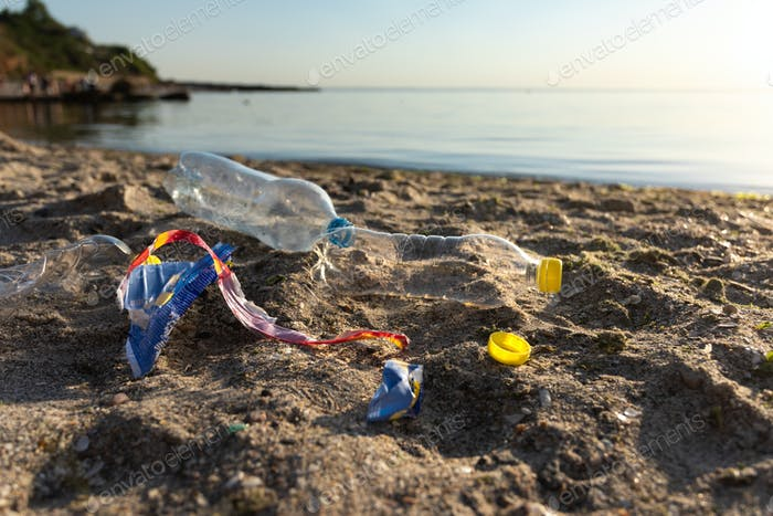 Polluted Beach With Plastic Garbage Lying On Sand Near Water