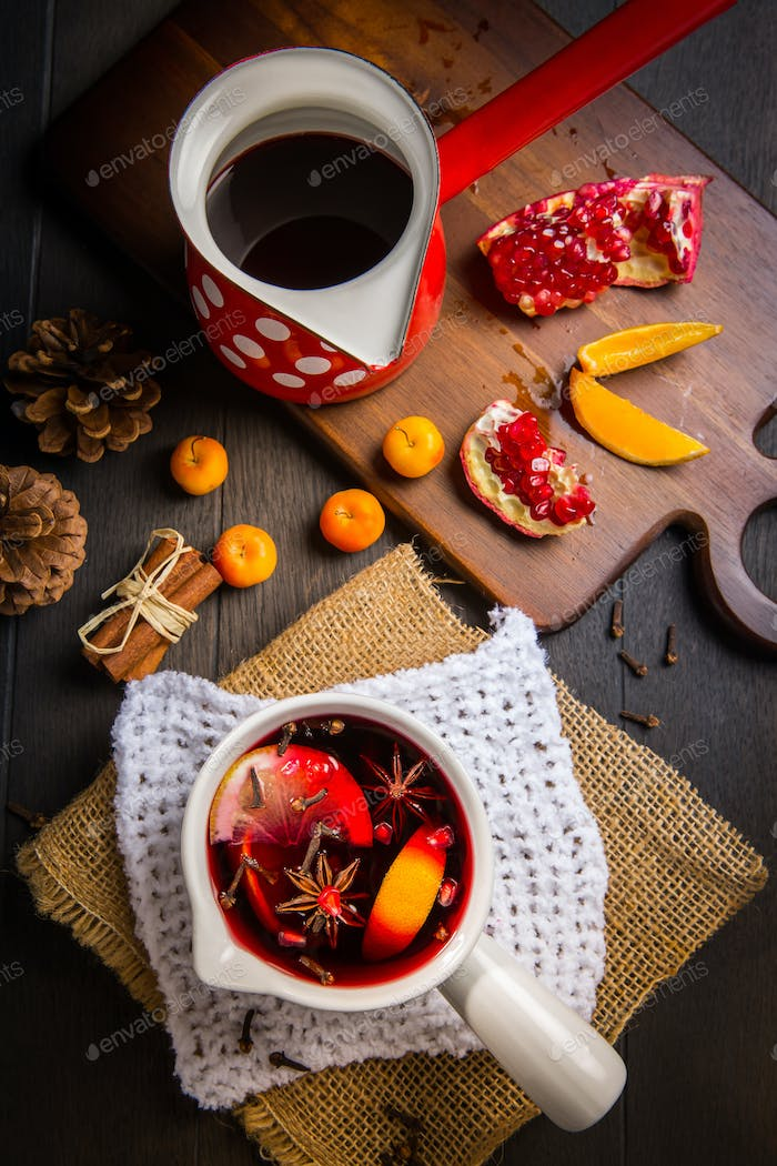 Hot spicy mulled wine with fruits and spices in mug