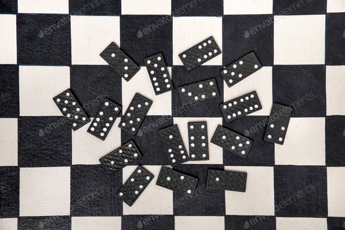 Scattered black domino tiles on a chessboard