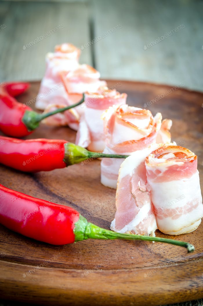 Rolled bacon strips on wooden board