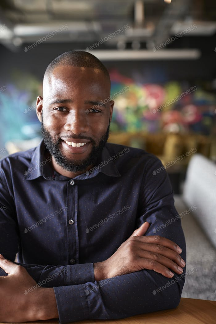 Mid adult black male creative sitting at a table in an office cafe smiling to camera, close up, crop