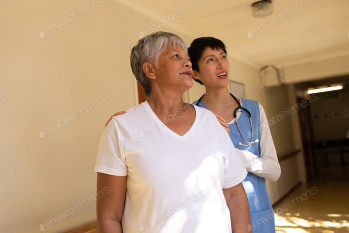 Senior female patient and Asian female nurse standing in corridor at retirement home