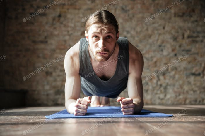 Serious strong sportsman in gym make yoga sport exercises.