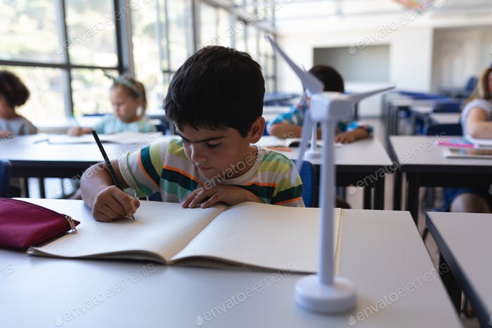 Front view of schoolboy writing on notebook at desk in classroom of elementary school