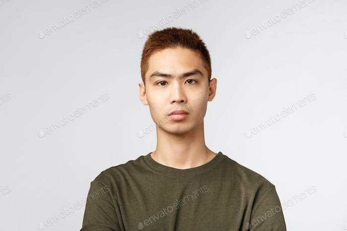 Close-up portrait of serious-looking japanese guy in green t-shirt, look serious and determined