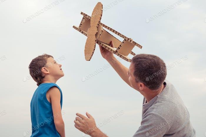 Vater und Sohn spielen mit Pappe Spielzeug Flugzeug
