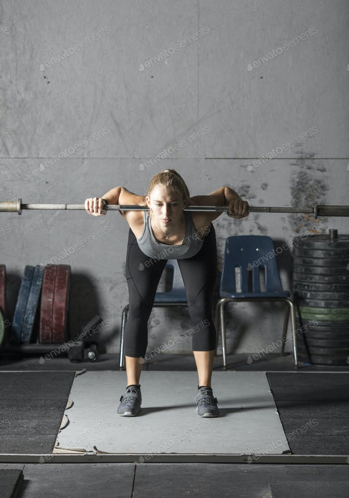 Strong young woman warming up in preparation for heavy lifting in gym,