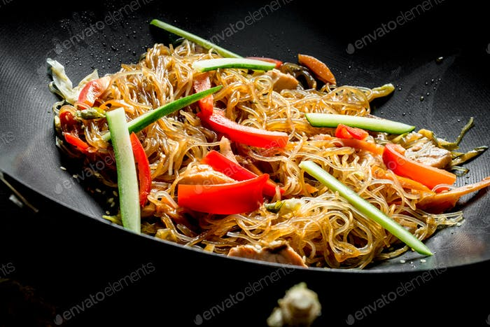 Chinese wok. Cooking Asian funchoza with chicken and vegetables in a frying pan wok.