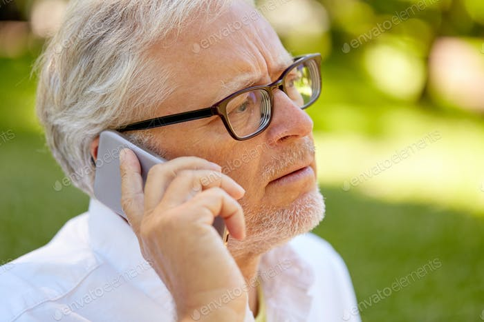 senior man in glasses calling on smartphone