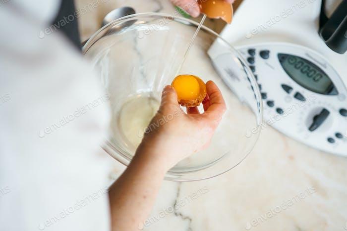 Woman breaking egg in bowl