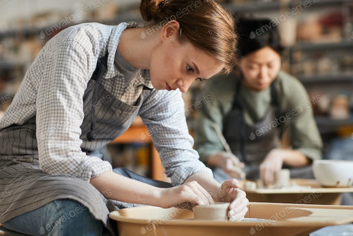 Serious woman making pot in workshop