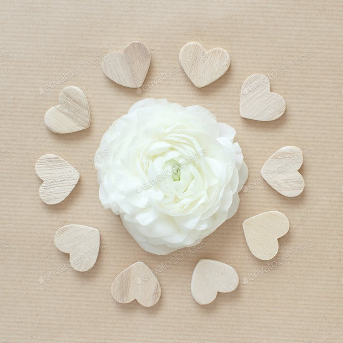 Cream flower in a circle of hearts on beige paper