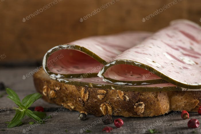 sandwich with specialty ham or salami made with pork meat and sheep cheese