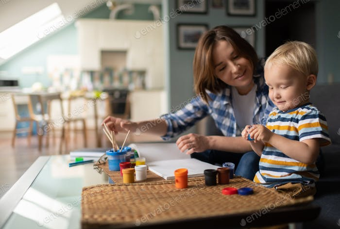 Satisfied mother and son drawing together at home