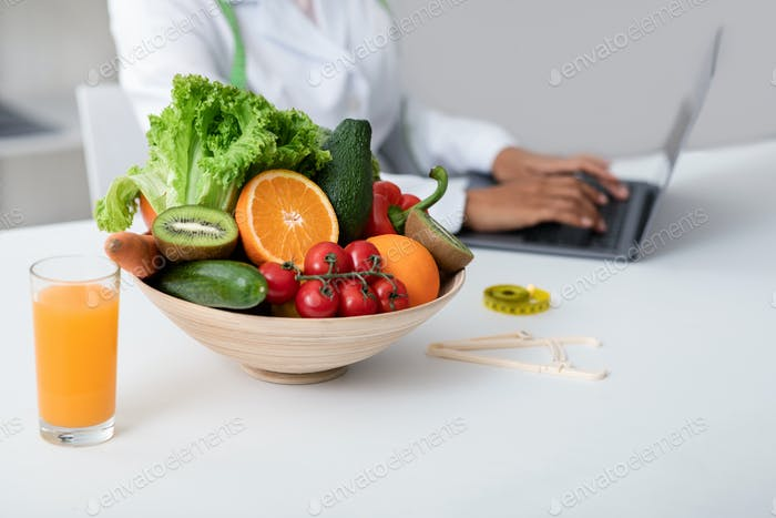 Side view of nutritionist working with laptop at clinic