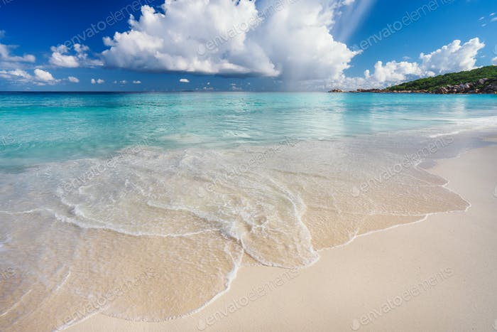 Ocean wave and cloudscape on tropical beach Grand Anse, La Digue Island, Seychelles