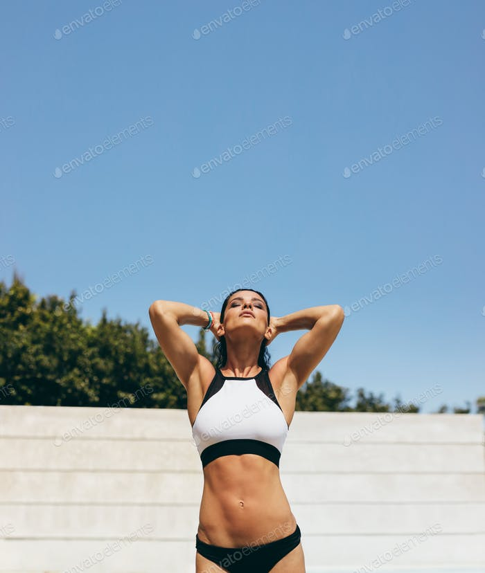 Healthy female athlete in swimwear at poolside