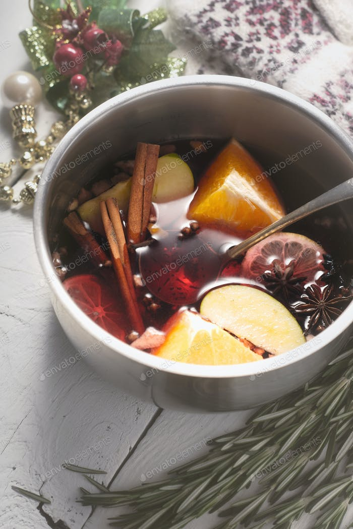 Mulled wine with different spices  and fruits in the pot top view