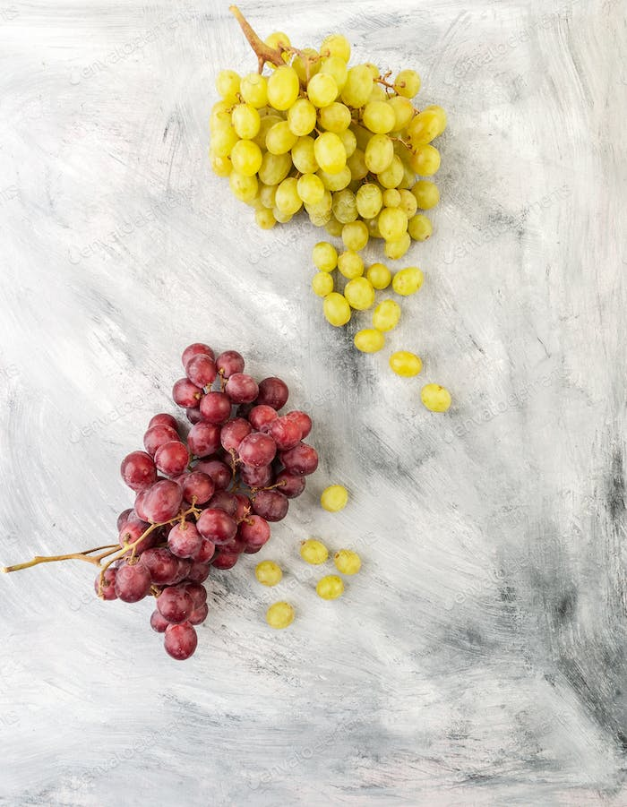 White and red grapes on a gray old table.