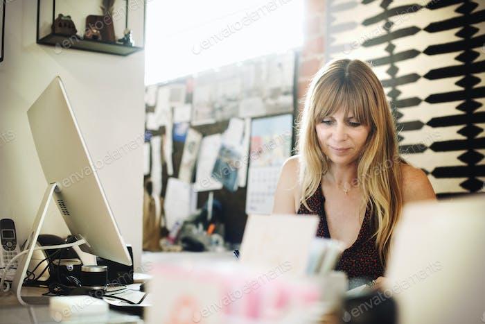 Frau sitzt in einem Büro an einem Schreibtisch mit einem Computer, arbeitet.