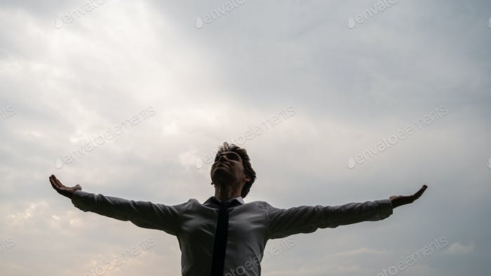 Young businessman standing under cloudy grey sky aith his arms spread widely