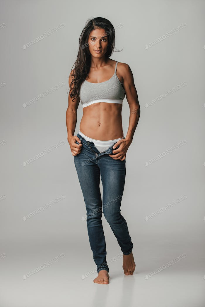 Grinning young woman in unzipped blue jeans