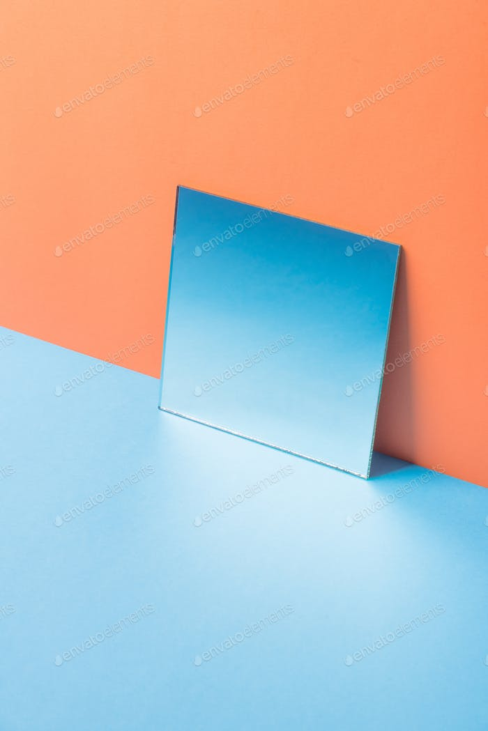 Mirror on blue table isolated over orange background