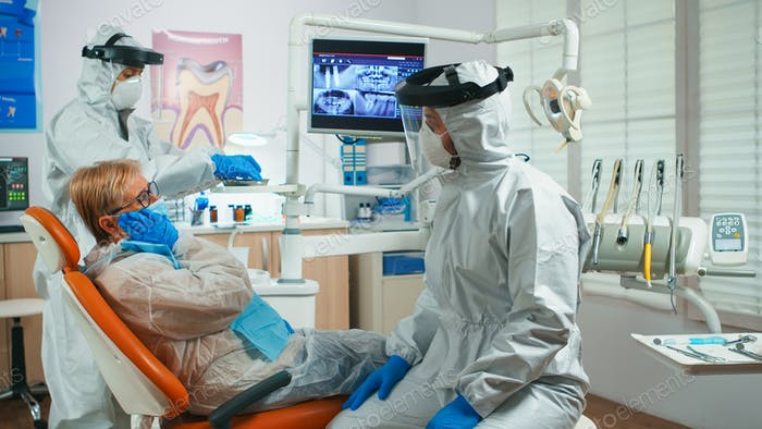 Senior woman showing aching tooth to dentist dressed in coverall