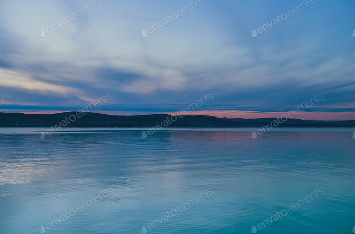 Evening view of the lake and mountains at sunset, blue hour. Balaton, Hungary.
