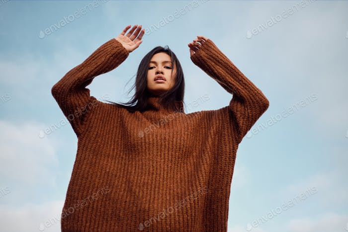 Gorgeous stylish Asian girl in cozy knitted sweater sensually looking in camera posing over sky
