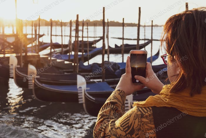Over the shoulder view of woman taking picture of gondolas moored in the Canale Grande in Venice,