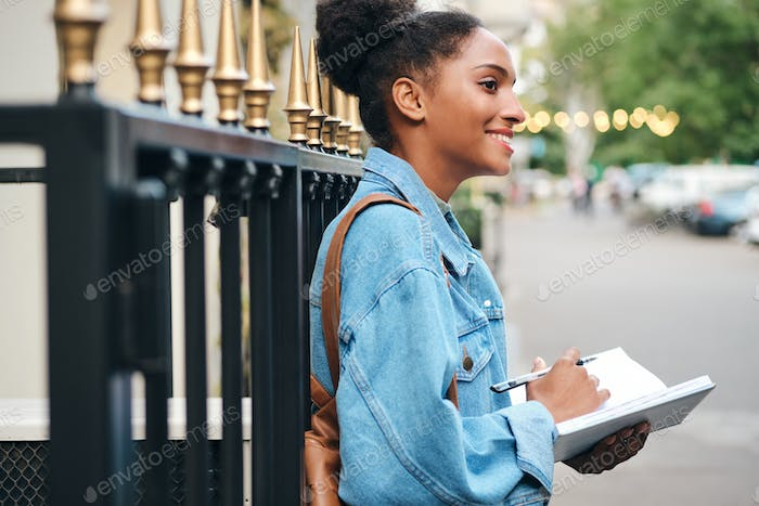 Beautiful African American student girl in denim jacket with notepad happily studying on city street