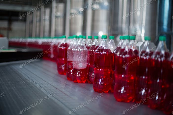 Bottles of juices processing on conveyor belt in factory