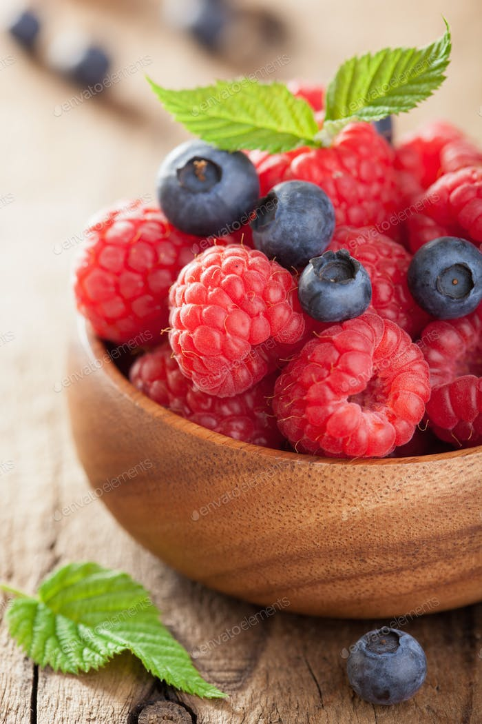 fresh berries raspberry blueberry in wooden bowl