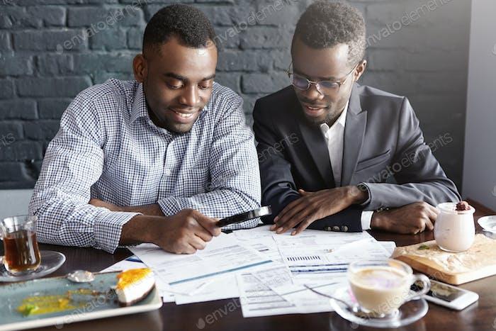 Dos apuestos empresarios afroamericanos exitosos usando lupa mientras estudian documentos