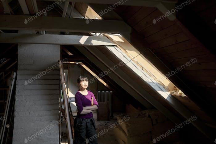 Женщина в старом чердаке смотрит на солнечный свет