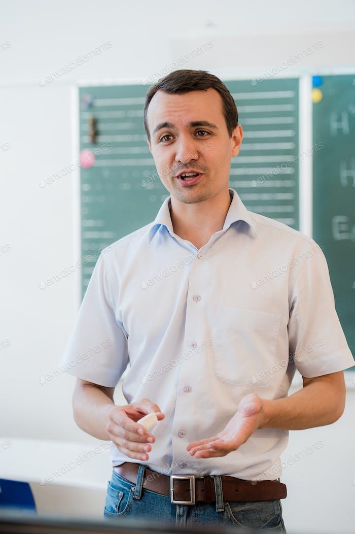 Young teacher near chalkboard in school classroom talking to class