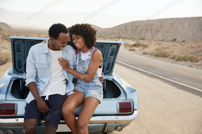 Couple Sitting In Trunk Of Classic Car On Road Trip