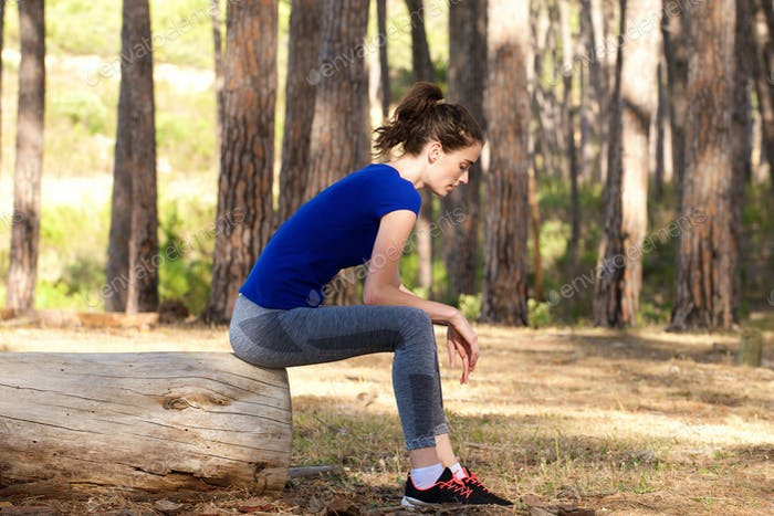 Young sporty woman resting on log outside