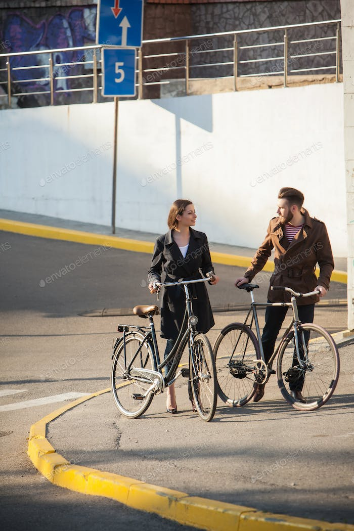 Young couple with on a bicycle opposite city