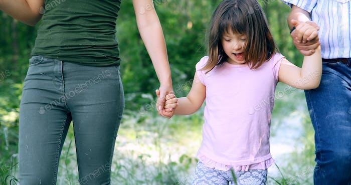 Schönes kleines Mädchen mit Down-Syndrom zu Fuß mit Eltern