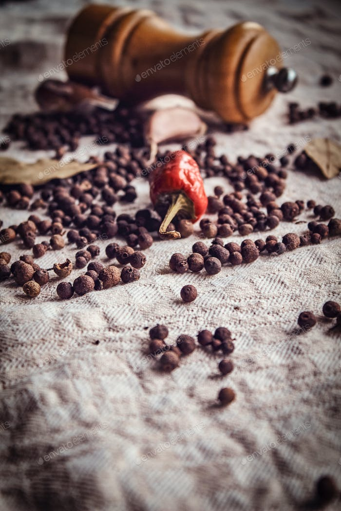 Close-up photo of the fruits of black pepper, red pepper and garlic on linen fabric