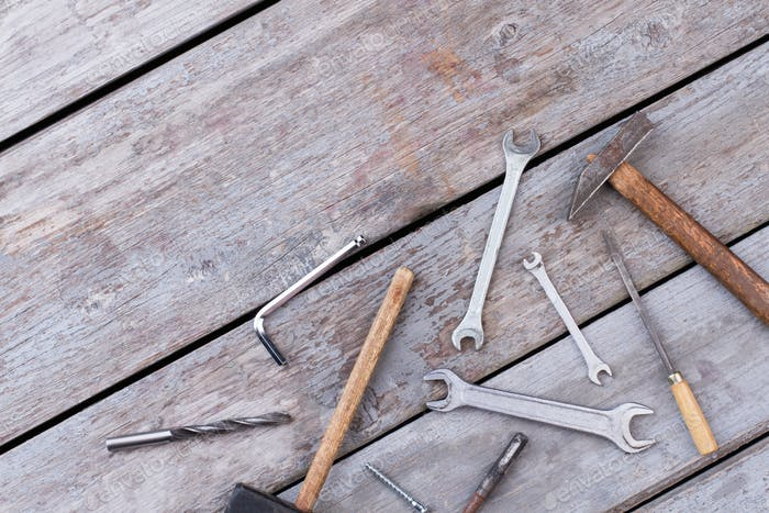 Different construction tools on wooden background.
