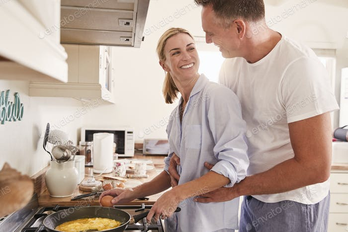 Affectionate Mature Couple Prepare Breakfast In Kitchen Together